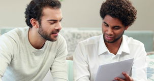 Gay couple using calculator paying bills. In living room stock video footage