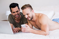 Gay couple using smartphone and laptop. Lying in bed Stock Image