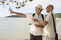 Gay couple on vacation pointing at destination Stock Image