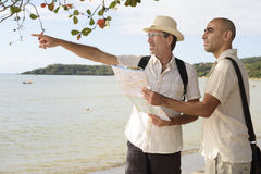Gay couple on vacation pointing at destination Royalty Free Stock Images