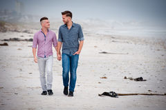 Gay couple walking holding hands royalty free stock photography