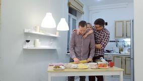 Gay family with daughter kid cook pizza together in the kitchen and hugging. Gay family with daughter kid cook pizza together in the kitchen and hugging stock video
