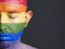 Gay flag painted on face man closed eyes. Gay flag painted on the face of a man.The man's eyes are closed with a serene expression on his face Stock Photo