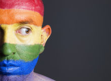 Gay flag painted on face man. looking sideways. Gay flag painted on the face of a man. Man is looking sideways with restlessness expression Stock Images