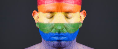 Gay flag painted on the face of a man. The man's eyes are closed with a serene expression on his face Royalty Free Stock Photography