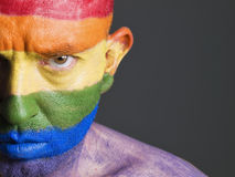 Gay flag painted face man, serious expression. Gay flag painted on the face of a man. Man is looking at camera and has a serious expression Royalty Free Stock Photo