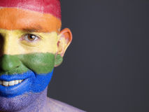 Gay flag painted on the face of a smiling man. Gay flag painted on the face of a man. Man is looking at camera and is smiling Stock Images