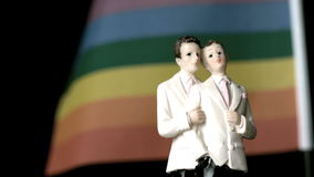 Gay groom cake toppers in front of rainbow flag moving in the wind Royalty Free Stock Photos