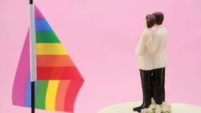 Gay groom cake toppers in front of rainbow flag revolving Stock Photography