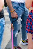Gay guy with Concept of sexual minority. Guy hand and arm with rainbow wristbands outdoors. pink dog leash in pride festival stock photos