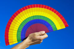 Gay hand fan. Someone holding a hand fan painted with the colors of the gay pride flag over the blue sky royalty free stock image