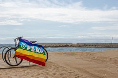 Gay and lesbian community flag on bicycle near the sea Royalty Free Stock Photography