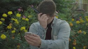 Gay looking in a mirror and combing. Young man combing hair with comb. Guy styling his hair. Gay on the background of a bed of flowers stock video footage
