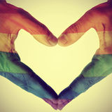 Gay love. Picture of man hands forming a hear patterned with the gay pride flag, with a retro effect stock photo