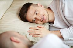 Gay lover. Happy and amorous young gay men lying on pillow and looking at his lover with smile Stock Photography