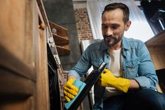 Gay male cleaner brightening surface. Inside cleaning. Low angle of charming professional male cleaner working with cleaning cloth while looking down and smiling Royalty Free Stock Image