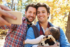 Gay Male Couple With Baby Taking Selfie On Walk In Woodland royalty free stock images