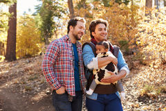 Gay Male Couple With Baby Walking Through Fall Woodland Royalty Free Stock Photography