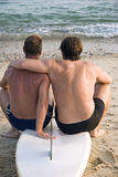 Gay male couple embracing. A colour portrait of a gay male couple sitting on a surfboard along the beach and cuddling.They are both sportsman and have athletic Stock Images