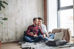 Homosexual partners working at office desk, relationships and business concept. Gay male couple sitting at home choosing rings for same-sex marriage ceremony stock image