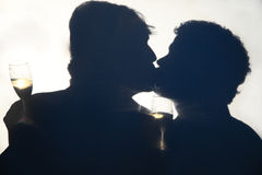 Gay Male Kiss Silhouette. Silhouette of gay men kissing on their wedding day, holding champagne glasses behind an opaque screen Stock Image