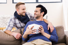 Gay man offering present to his boyfriend Stock Photography