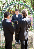 Gay Marriage Ceremony. Gay couple being married by their minister outdoors under a floral archway Royalty Free Stock Photography