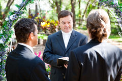 Gay Marriage Ceremony. Minister performing marriage ceremony for two grooms at a gay wedding Royalty Free Stock Photography