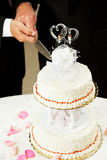 Gay Marriage - Cutting Wedding Cake. Closeup of a wedding cake topped with two grooms, being cut by two men's hands Royalty Free Stock Photos