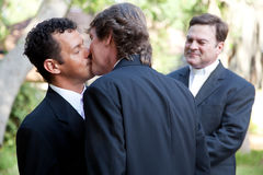 Gay Marriage - Kiss the Groom. Wedding of handsome gay male couple.  The grooms kiss as the minister looks on Stock Images