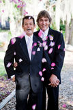 Gay Marriage - Showers of Petals. Gay wedding couple being showered with rose petals Royalty Free Stock Photo