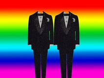 Gay Marriage. Two tuxedos standing together in front of a rainbow background Stock Image
