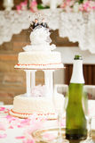Gay Marriage - Wedding Cake. Wedding cake decorated with two grooms, on a reception table with champagne and rose petals Royalty Free Stock Photos