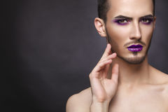 Gay. Pretty sensual fashion man with art makeup and beard. Pretty sensual gay man with art makeup and beard. Color syringe in the hand Royalty Free Stock Images