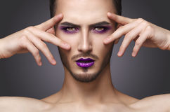 Gay. Pretty sensual fashion man with art makeup and beard. Pretty sensual gay man with art makeup and beard posing on camera in the photostudio stock image