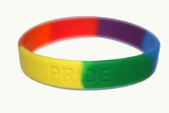 Gay pride. Rainbow gay pride colourful bracelet on black background royalty free stock photo