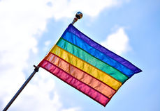 Gay Pride Flag. Rainbow Gay Pride Flag waiving on sunny cloudy blue sky background royalty free stock photos