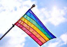 Gay Pride Flag. Rainbow Gay Pride Flag waiving on sunny cloudy blue sky background royalty free stock photography