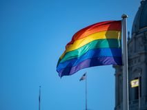 Gay pride flag waving in air with United States flag in backgrou royalty free stock image