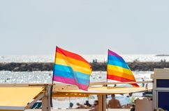 Gay pride flags blowing in the wind on Sitges Beach, Spain. Gay pride flags blowing in the wind on Sitges, in Barcelona province. Perhaps Spain top gay stock photo