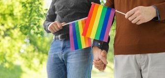 Male couple with gay pride flags holding hands. Gay pride, lgbt and homosexual concept - close up of happy male couple with rainbow flags holding hands over stock photography