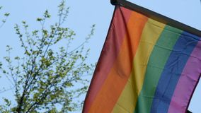 Gay pride rainbow flag LGBT flying. A multi-colored rainbow flag, a symbol of unconventional traffic, sways in wind in. Gay pride rainbow flag LGBT flying. A stock video footage