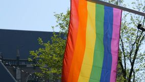 Gay pride rainbow flag LGBT flying. A multi-colored rainbow flag, a symbol of unconventional traffic, sways in wind in. Gay pride rainbow flag LGBT flying. A stock footage