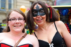 Gay Pride Rally and March on 23rd May 2015. Two women at Gay Pride rally in Birmingham England one in mask smiling Royalty Free Stock Image