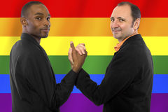 Gay Pride. Same-sex homosexual couple with a rainbow gay pride flag in the background royalty free stock photos