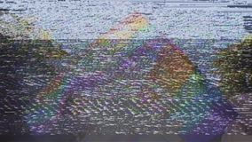 Gay pride in slow motion dancing LGBT lesbian and gay gender flags. Old vhs vintage film tape effect over Lesbian and gay gender symbols on two gay rainbow flag stock video