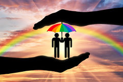 Gay rights notion. Icons of two gays with a rainbow umbrella in hand on a background of iridescent sky Royalty Free Stock Photography