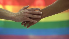 Gay stroking partner hand lgbt flag background, rights equality pride march. Stock footage stock video