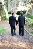 Gay Wedding Couple Walking on Garden Path. Two gay male grooms walking hand in hand down a garden path together. Symbolizes the pathway of life. Some motion blur stock photography