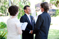 Gay Wedding - Female Minister. Gay male couple gets married by a young female minister in a beautiful outdoor wedding ceremony royalty free stock images